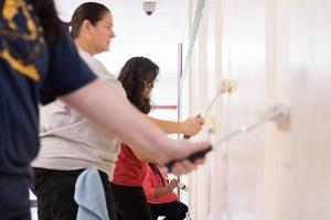 Baxter employees painting a wall